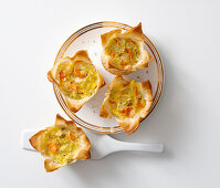 Filo pastry baskets with vegetables and cheese sauce