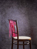 Homemade beetroot pasta drying on a wooden chair