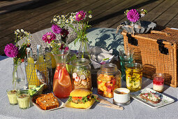 Various drinks and snacks for a summer picnic by a lake