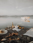 Bottle of sparkling wine, glasses, sunhat, sandals and blanket on rocky lake shore
