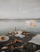 Bottle of sparkling wine, glasses, sunhat, sandals and blanket on rocky lake shore