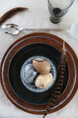 Feather and marbled eggs in glass bowl on brown plate