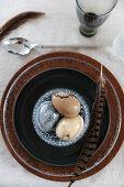 Feder und marmorierte Eier im Glasschälchen auf braunem Teller
