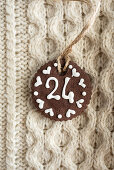 A chocolate biscuit with white writing icing on a knitted jumper