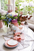A table laid with crockery, wine and flowers in front of a window