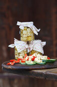 Preserved cream cheese in jars and on cucumber, tomatoes and peppers