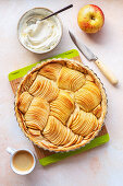 Apple tart with whipped cream and a cup of coffee on the table