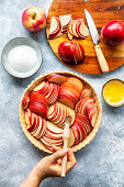 Preparation of an apple tart: Hand brushing sliced apples with melted butter