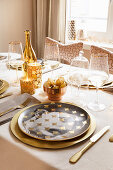 Table festively set in gold and white with portrait plates