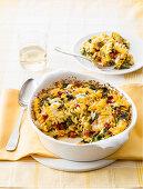 Fusilli casserole with salami, romaine lettuce and arugula