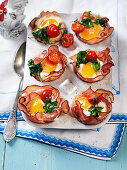 Easter eggs baked in ham with spinach and tomato
