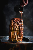 Melted chocolate flows on stacked slices of banana bread