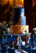 Tiered cake in dark blue and gold on glass cake stand