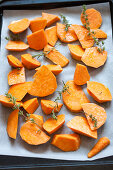 Sweet potatoes with thyme on a baking tray