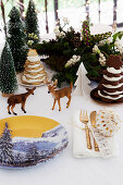 Christmas arrangement with china plate painted with winter landscape motif on table