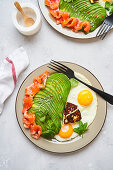 Healthy breakfast with fried eggs, salmon and avocado