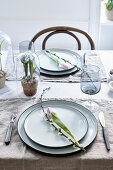 Tulips and willow catkins on plates on set table