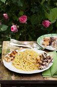 Spaghetti with grilled seafood skewers