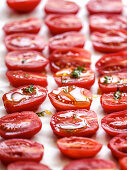 Date tomatoes with olive oil and herbs on a baking tray