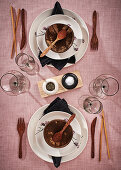White place settings with coconut shells, chopsticks and wooden cutlery
