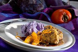 Pork medallions on blue mashed potatoes with orange fillets
