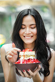 Young Asian woman eats a tiramisu strawberry ice cream sundae in a street cafe in Bangkok
