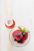 Purple scoops of ice cream in glass bowl with fresh blueberry and mint