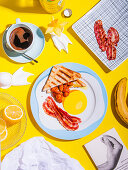 Breakfast with toast, baked beans and bacon on a plate with a fried egg motif