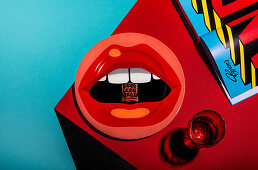 A piece of tiramisu on a plate with a pop art lip motif