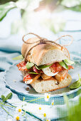 Baguette sandwich with bacon, chicken breast fillet and mozzarella