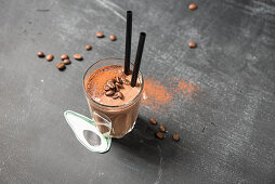 A coffee and chocolate smoothie with a straw in a glass