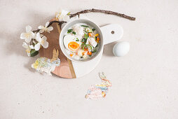 Fanesca (Easter soup, Equador) decorated with a sprig of blossom and paper bunnies