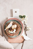 Easter decoration: an Easter nest decorated with a spring of blossom and homemade paper birds