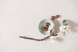Chocolate eggs in a bowl decorated with paper butterflies and a sprig of blossom