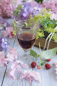 A glass of raspberry liqueur with hydrangeas and raspberries