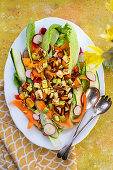 Spring salad with avocado, carrots, courgettes, radishes and pine nuts