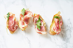 A set of bruschettas with cured meat, pear, blue cheese and ruccola