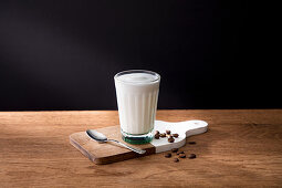 Glass of fresh milk on wooden board with spoon and coffee grains
