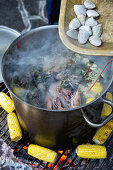 Seafood in a saucepan and corn cobs on a grill