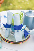 Handmade napkin rings with blue bird motifs on table set for summer meal in garden