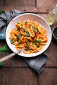 Vegan penne with lentil and carrot bolognese, wild garlic, sesame and yeast flakes