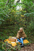 Young woman picnicking in a forest