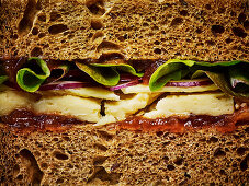 A ploughmans cheese sandwich on bown bread, close up