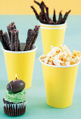 Cupcake with a candle, biltong stripes and popcorn for a rugby party