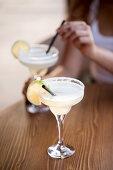 Zwei Cocktails mit Limettenscheiben auf Holztisch