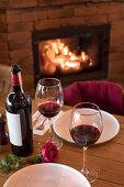 Zwei Rotweingläser mit Flasche und roter Rose auf Holztisch vor Kamin