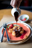 Profiteroles with melted chocolate pouring from saucepan and fruit