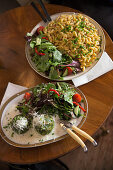 Cheese spätzle (soft egg noodles from Swabia) and spinach dumplings each with a side salad