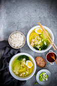 Bowls with Chinese soup with pak choi, chicken, ginger, potatoes and spring onions, boiled eggs and sesame seeds