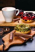 Assorted delicious doughnuts with glaze and toppings composed with chocolate bars and cup of coffee on wooden boards